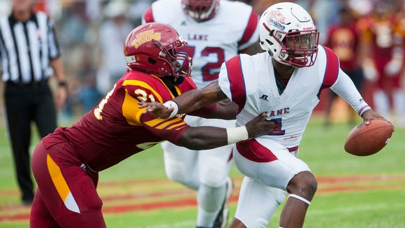 Tuskegee's Daryl George (21) stops Lane quarterback Marcus Reynolds (1) in Tuskegee, Ala., on Saturday September 24, 2016.