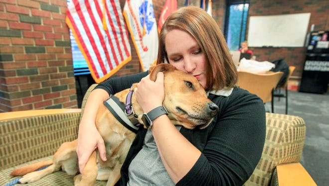 Sarah Sell, director of veteran student services at Wichita State University, cuddles with her rescue dog Riley, which she is training to be a therapy dog.