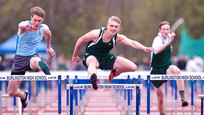 St. Johnsbury's Ian Clough, center, clears the final hurdle en route to winning the boys 110 meters at the Burlington Invitational track meet on Saturday at D.G. Weaver Athletic Complex.