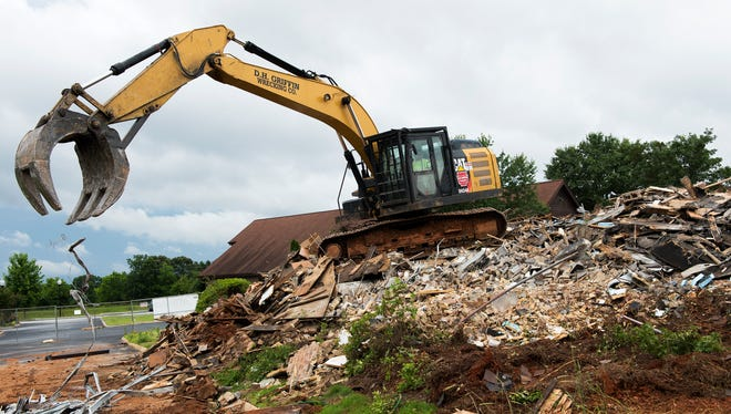 An excavator digs through rubble at Advent United Methodist Church on Wednesday, May 24, 2017. Cleanup efforts have begun at the church's sanctuary building, which burned down in February.