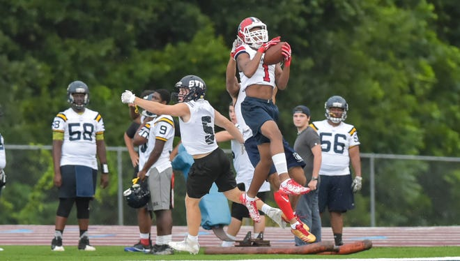 Andrew Simon, senior wide receiver for Comeaux, catches a ball over St. Thomas More defenders as the teams participate in the QuickSlants 7-on-7 football tournament at St Thomas More on Thursday.