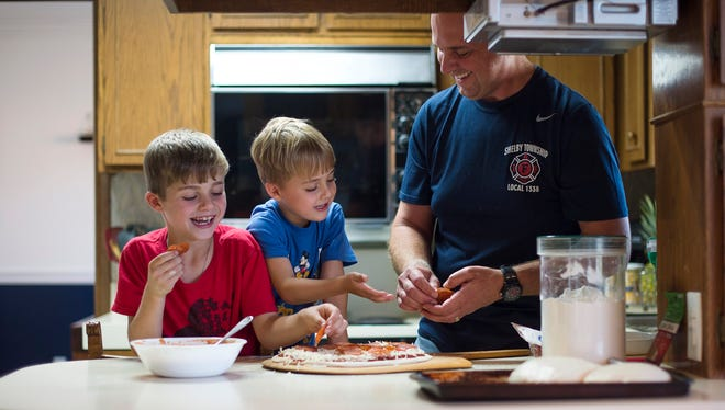 """From left, brothers Michael Tidrow, 8, and Andrew Tidrow, 5, laugh with their father, Matt Tidrow, as they prepare to make pizzas for dinner on Saturday, Sept. 16, 2017 at their house in Shelby Township. Matt Tidrow is the co-founder of """"Just Add Tomatoes"""", a spice blend for pizza sauce, which is available in Kroger stores across Michigan. Rachel Woolf, Special to the Free Press"""