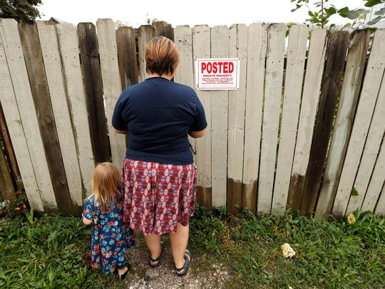 Tanya Keith, of Des Moines, and her daughter Iolana open a fence to their backyard to feed chickens. The trend of raising backyard chickens is causing a soaring number of illnesses from poultry-related diseases.