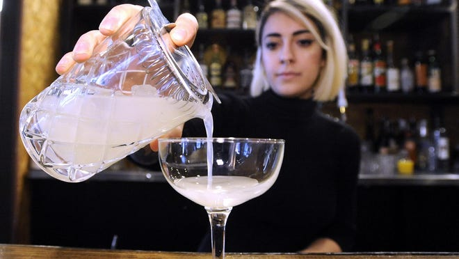 Anna Atanassova pours the mix into coupe glass. XXXXRock City Eatery beverage director Anna Atanassova, 23, of Detroit, makes a Oaxacan Milkshake, which is a warm mescal and coconut milk cocktail at the restaurant, Saturday afternoon, January 14, 2017. The ingredients are coconut milk, lemon grass, cinnamon, cardamom, Thai chili flakes, Lime Juice, raw ginger syrup and mescal. (Todd McInturf, The Detroit News)2017.
