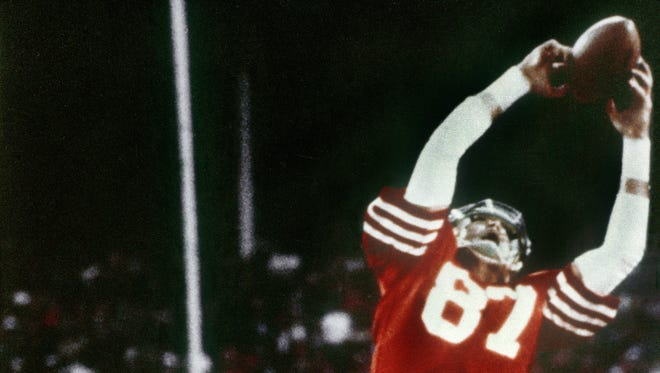 In this Jan. 10, 1982, file photo, Dallas Cowboys' Everson Walls, obscured at rear, defends as San Francisco 49ers' Dwight Clark leaps high in the end zone to catch a Joe Montana pass for a touchdown in the fourth quarter of the NFC Championship NFL football game at Candlestick Park in San Francisco.