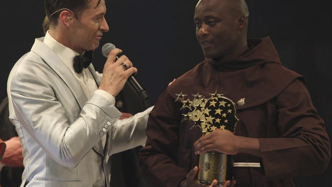 Kenyan teacher Peter Tabichi, right, listens to actor Hugh Jackman, after winning the $1 million Global Teacher Prize in Dubai, United Arab Emirates, Sunday, March 24, 2019. Tabichi is a science teacher who gives away 80 percent of his income to the poor in the remote Kenyan village of Pwani.