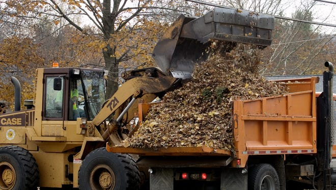 Town of Elmira Highway Department workers pick up leaves on West Church Street in West Elmira. Public works functions in the town and two other municipalities will soon be under the auspices of Chemung County.