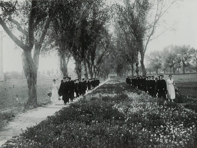 Students and professors approach commencement ceremonies by marching down the Oval. Photo taken in 1920.