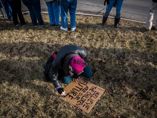 "A woman finishes a sign during the ""Save MCS"" rally at the intersection of McGalliard Road and Wheeling Avenue Friday evening."