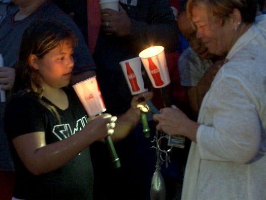 Brooklynn Rinck, 11, holds candles during a memorial