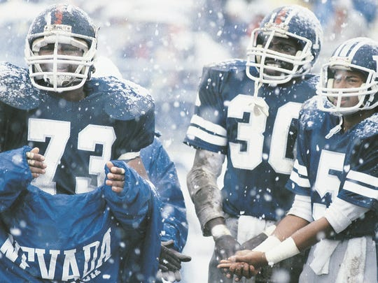 Three Wolf Pack players huddle together during the Snow Bowl in 1983.