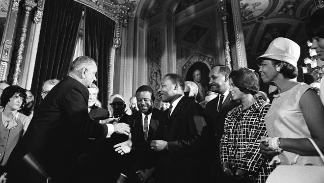 President Lyndon B. Johnson moves to shake hands with Dr. Martin Luther King after signing the Voting Rights Act in the Rotunda of the U.S. Capitol on Aug. 6, 1965.  But more than a half century later, more work lies ahead to secure the promise of the VRA.