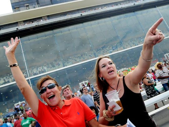 Kelly Collums, left, and Leslie Shaffer cheer when their horse wins a race during the Super Derby at Louisiana Downs Saturday evening. Henrietta Wildsmith/The Times Henrietta Wildsmith/The Times