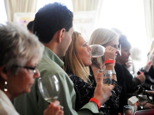 Festival-goers gather around a table to taste samples during the Winter Wine Festival on Saturday, Feb. 22, 2014, at the Stonewall Jackson Hotel in Staunton. The festival, in its fourth year, is hosted by the Historic Staunton Foundation.