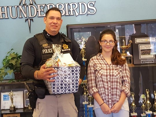 Mesilla Marshal's Department Officer Manuel Cortez receives an Officer Appreciation package from Zia Middle School student Cynthia Della-Ratta.