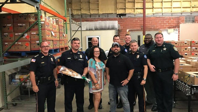 """Pensacola Police Officers and Escambia County Sheriff's Deputies celebrate the success of their """"doughnut strike,"""" which raised more than 25,000 pounds of food for needy local families."""