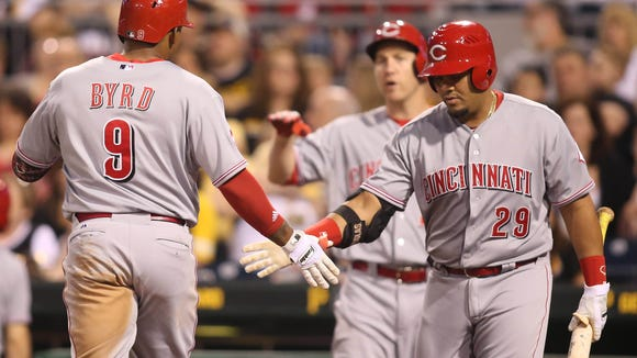 Reds left fielder Marlon Byrd (9) is greeted at home plate by first baseman Brayan Pena (29) after Byrd hit a solo home run against the Pittsburgh Pirates during the fifth inning Wednesday at PNC Park.