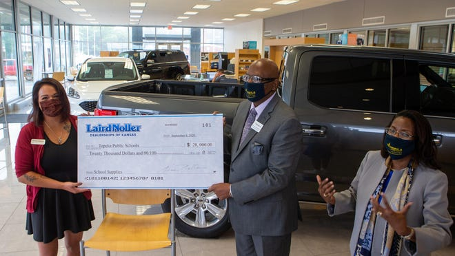 Chelsea Ramirez, left, with Laird Noller dealerships, presents a check for $20,000 to Larry Robbins, USD 501 deputy superintendent, and Tiffany Anderson, USD 501 superintendent, Tuesday afternoon at Laird Noller Ford, 2245 S.W. Topeka Blvd. The donation will go to purchasing school supplies, including mobile hotspots, for the district.