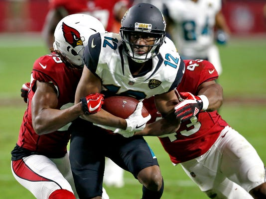 In this Sunday, Nov. 26, 2017  file photo, Jacksonville Jaguars wide receiver Dede Westbrook (12) is hit by Arizona Cardinals defensive back Tramon Williams (25) and inside linebacker Haason Reddick (43) during the second half of an NFL football game in Glendale, Ariz. Rookie receiver Dede Westbrook will wear purple cleats to raise awareness for domestic violence when the Jacksonville Jaguars (7-4) host the Indianapolis Colts (3-8) on Sunday, Dec. 3, 2017.  (AP Photo/Ross D. Franklin, File)