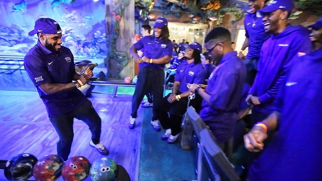 TCU's Dante Gray dances after scoring a strike while bowling with the team at the lanes at Bass Pro Shops in downtown Memphis during a welcome party for the AutoZone Liberty Bowl teams Monday night. TCU and Georgia were treated to dinner and bowling in The Pyramid.