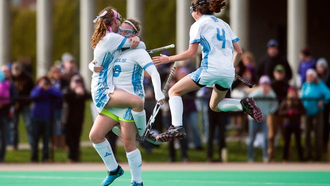 South Burlington's Casey Johnson, center, celebrates with teammates after scoring the game-winner in overtime to win the Division I high school field hockey state championship.