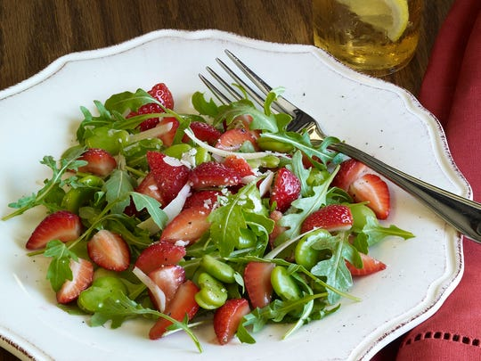 Arugula, fava beans and strawberries are dressed lightly with vinaigrette and topped with shaved pecorino.