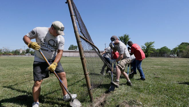 Veteran Jordan Daniel, left, and volunteers work on dismantling an old fence, Monday, June 27, 2016, in Detroit. Daniel is one of hundreds of veterans who are in the financially troubled city for a week to rebuild areas that have been neglected by poverty, crime and a lack of resources. It's the latest and largest effort undertaken by St. Louis-based The Mission Continues, which encourages and aids volunteerism by disabled and wounded veterans. (AP Photo/Carlos Osorio)