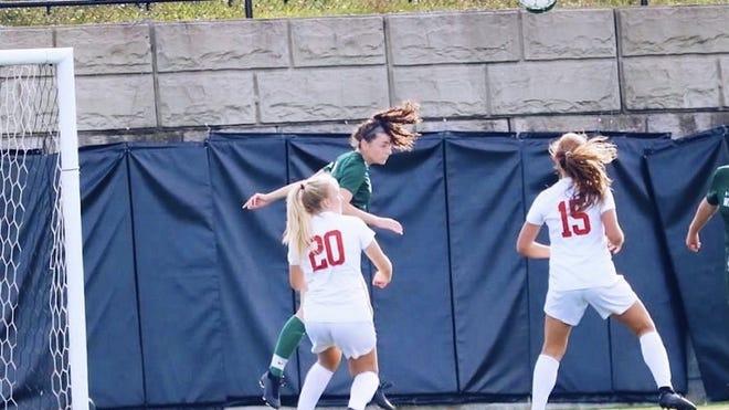 Wachusett Regional High School's Olivia Berglund, in green, heads a ball away from opponents.