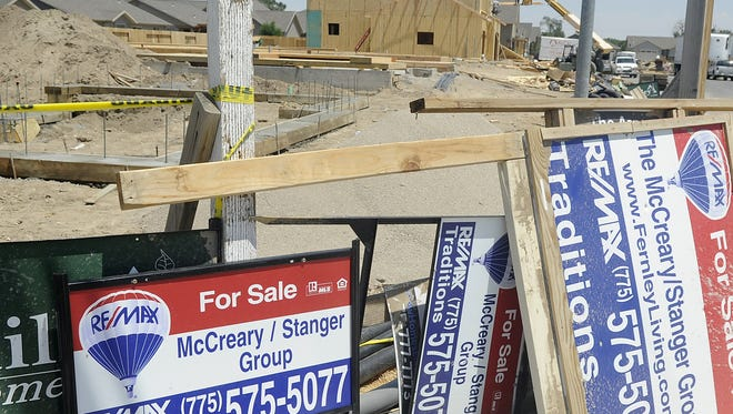 "A stack of ""for sale"" signs are piled up in front of a residential construction site in Fernley."