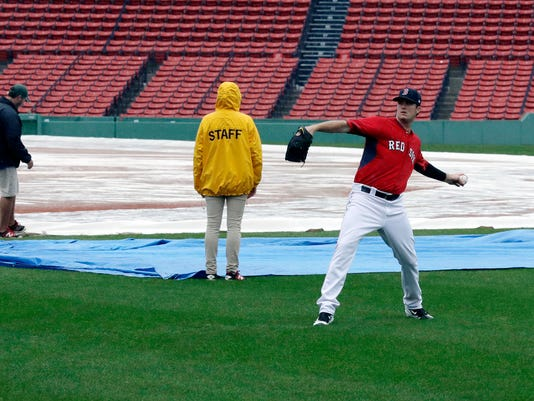 Boston Red Sox pitcher Drew Pomeranz tosses a baseball in the outfield in front of grounds crew workers at Fenway Park, Sunday, Oct. 9, 2016, in Boston. Rain postponed Sunday's scheduled Game 3 of baseball's American League Division Series between the Cleveland Indians and the Red Sox until Monday. (AP Photo/Charles Krupa)