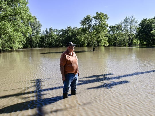 Mayor Harlin Clements stands in floodwater in Mosby, Mo. Residents have become accustomed to countless floods.