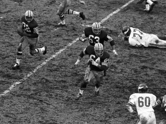Running back Elijah Pitts (22) runs the famous Packers sweep behind guards Fuzzy Thurston (63) and Jerry Kramer (64) during a 24-19 win over Minnesota at Lambeau Field on Dec. 6, 1965. Vikings linebacker Roy Winston (60) is at lower right, with defensive tackle Gary Larsen (77) on the ground.