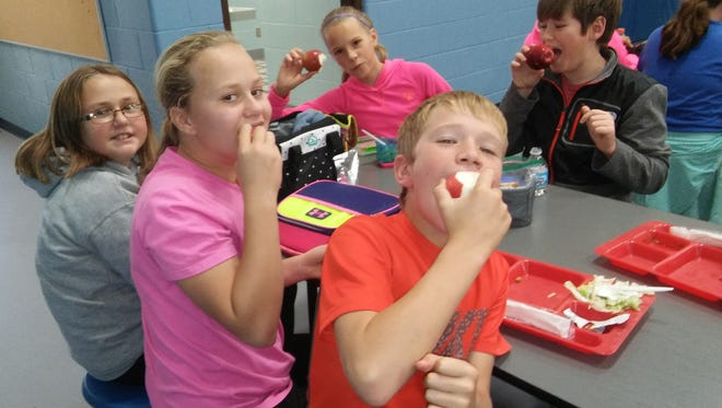 Students from Monroe Elementary School enjoy apples from Shoop's Orchard during last year's Great Apple Crunch event organized by the Farm to School movement in Manitowoc County.