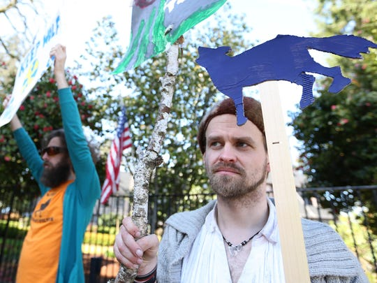 Jonathan Grindell, left, Zed Bailey and fellow protesters rally in support of wolves on Thursday, March 17, 2016, outside of Mahonia Hall in South Salem, Ore. The group is opposed to a bill signed into law by Gov. Kate Brown this week that impedes legal challenges to the state's decision to prematurely strip protections from gray wolves.
