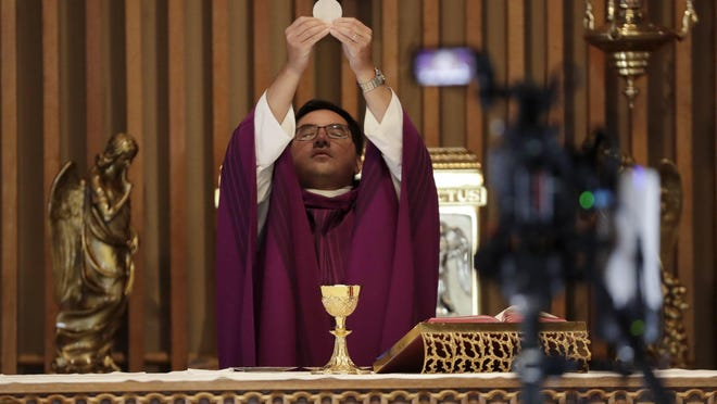 ST. AUGUSTINE, Fla. -- Father Phillip Tran performs during a live-streamed mass at the St. Augustine Church & Catholic Student Center on March 29. Like many houses of worship, on-site services open to parishioners have been suspended due to the new coronavirus pandemic.