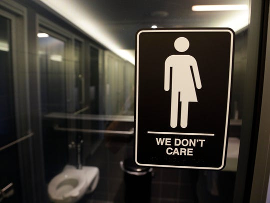 """This Thursday, May 12, 2016, file photo, shows a sign outside a restroom at 21c Museum Hotel in Durham, N.C. The Associated Press has determined that North Carolina's law limiting LGBT protections will cost the state more than $3 billion in lost business over a dozen years.That's despite Republican assurances that the """"bathroom bill"""" isn't hurting the economy."""