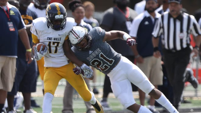 Detroit East English Village's Elija Griffin is tackled by River Rouge safety Reggie Pearson Jr. during their game on Saturday, Aug. 26, 2017 ,at Tom Adams Field in Detroit.