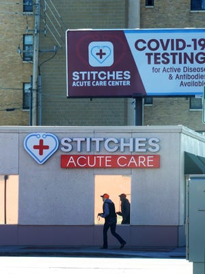 A woman walks past an urgent-care clinic offering coronavirus tests in downtown Cheyenne, Wyoming, on Nov. 16, 2020.