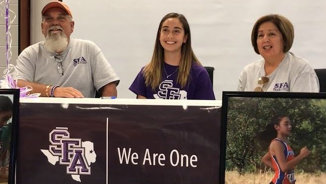 Central High School's Bailey Kinney, center, her father Billy and mother Gloria, celebrate Kinney's signing a letter of intent to run cross country and track for Stephen F. Austin Monday at the McCutchen Room at San Angelo Stadium fieldhouse.