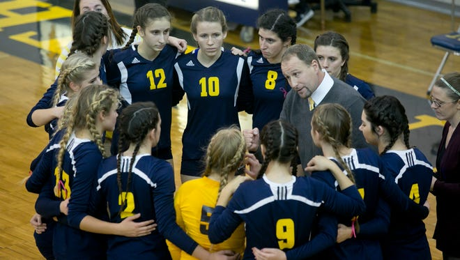 Port Huron Northern coach Tim Langolf talks with players in a huddle during a volleyball game in 2015 at Port Huron Northern High School.