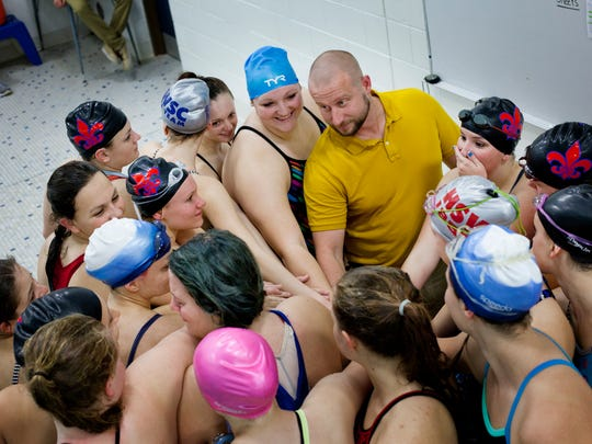St. Clair High School coach Kenny Sygit puts his hand into a huddle with his athletes as the Saints' star-studded swimming and diving team wraps up a practice.