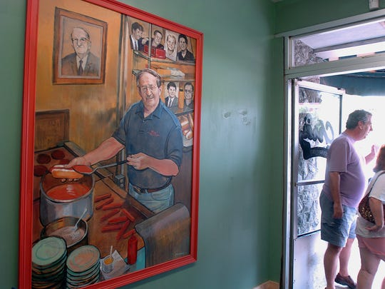Patrons of Chris' Hot Dogs on Dexter Ave. walk past a portrait of the restaraunt's owner, Theo C. Katechis, painted by artist Bob Adams.