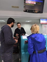 A Tunisian Airlines employee instructs a Tunisian couple