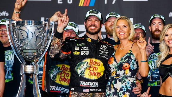 Martin Truex Jr., left, and girlfreind Sherry Pollex, celebrate after Truex won the 2017 Monster Energy NASCAR Cup Series championship.