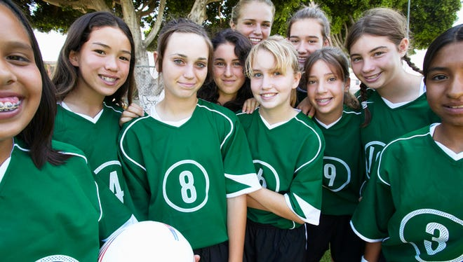Girls football team, smiling.