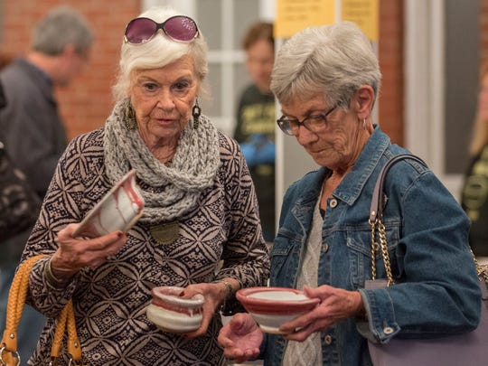 Winnie Kempf (left) and Connie Latham discuss which pottery pieces they would like to purchase during the Empty Bowls event to benefit Evansville hunger-based charities held at Sauced in Hayne's Corner Art District on Saturday morning.