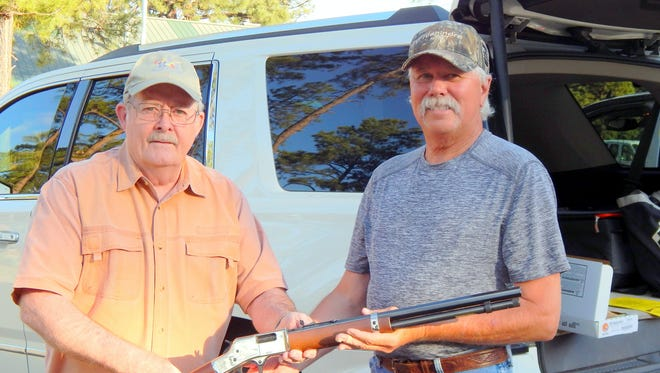 Ruidoso Noon Lion Don Fowler, left, presents the rifle to winner Jerry Ross of Ruidoso.