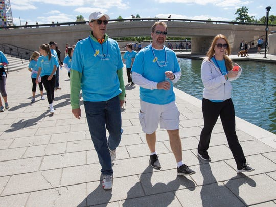 Michael Reikhof (center) was one of the participants who walked on Saturday, Sept. 13, 2014, in memory of his daughter, Peyton Reikhof, during the Out of the Darkness walk at White River State Park in Downtown Indianapolis. The event was a fundraiser for the American Foundation for Suicide Prevention.