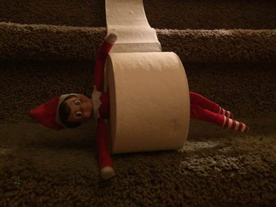 Elf on the Shelf goes on a ride down the stairs in a toilet paper roll.