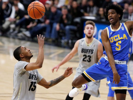 Colorado guard Dominique Collier, left, reaches for the ball after his shot was blocked by UCLA guard Chris Smith in the second half of an NCAA college basketball game Sunday, Feb. 25, 2018, in Boulder, Colo. (AP Photo/David Zalubowski)